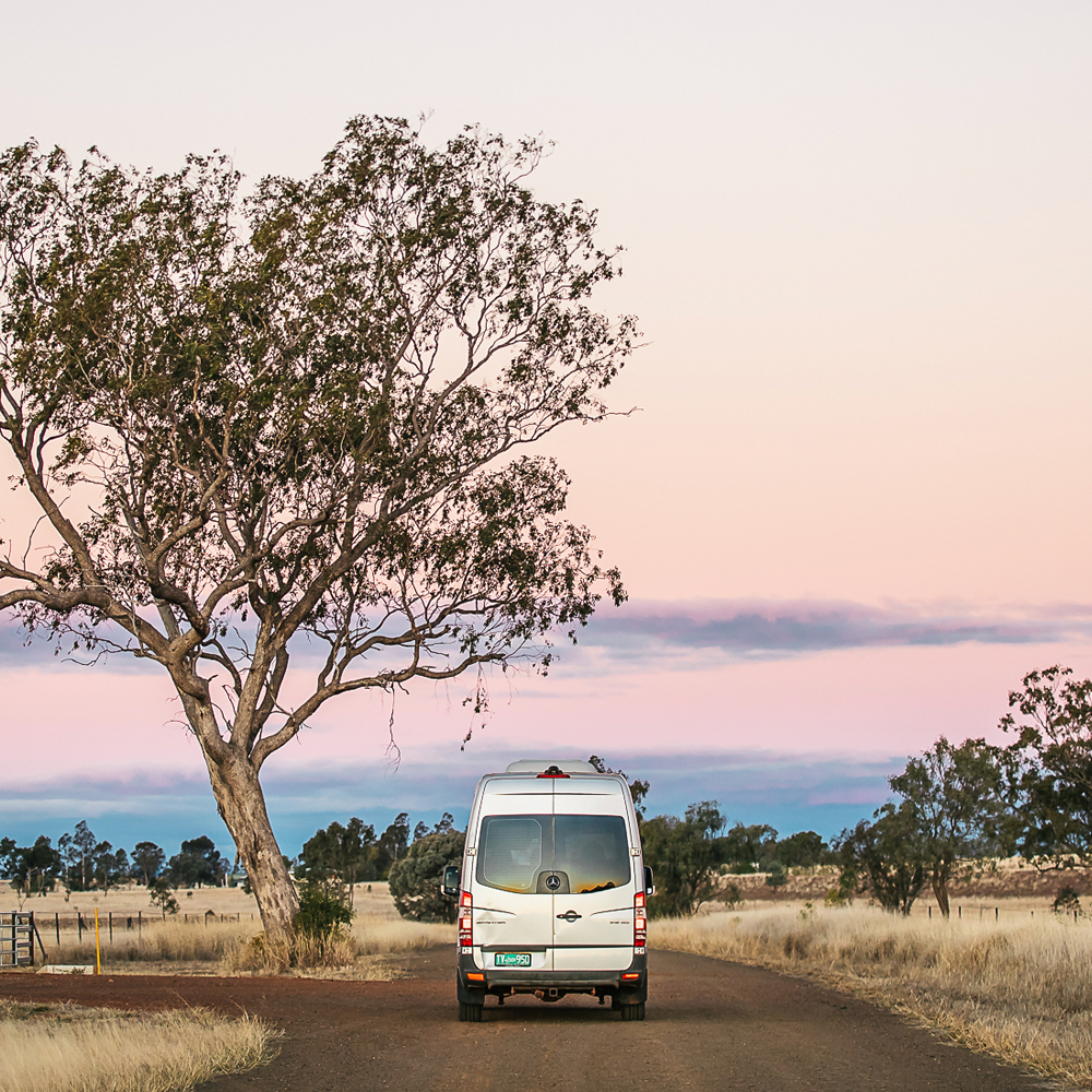 Van driving in the outback at sunset