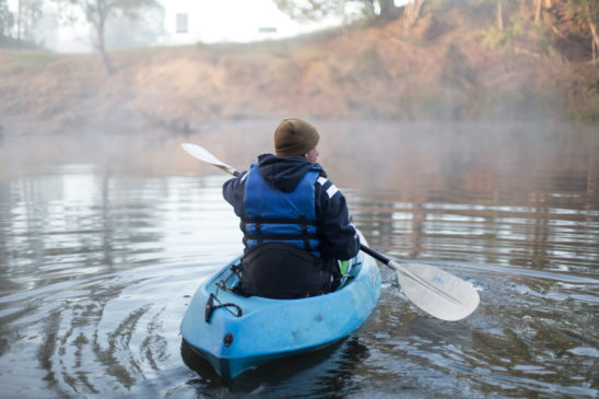 Man kayaking in river with mist