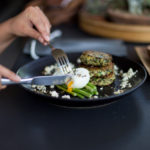 Cutting into Quinoa and spinach fritters with asparagus and soft boiled eggs