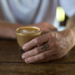 Hand holding a piccolo coffee at Betelnut Cafe