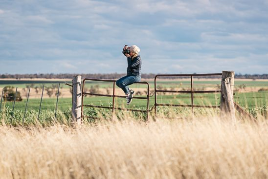 Photographer sitting on farm gate